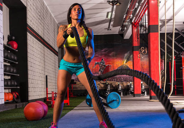 bikini competitor using battle ropes for weight loss