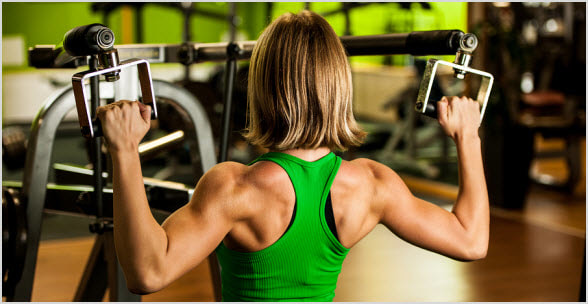 Muscular female performing lat pulldowns